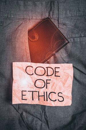 Word writing text Code Of Ethics. Business photo showcasing basic guide for professional conduct and imposes duties Small little wallet inside man trousers front pocket near notation paper