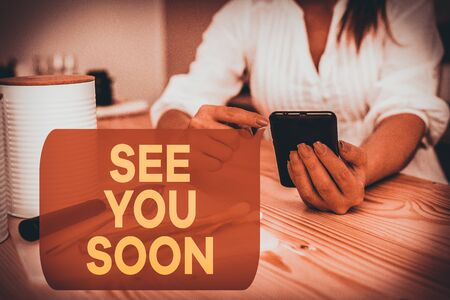 Writing note showing See You Soon. Business concept for used for saying goodbye to someone and going to meet again soon woman using smartphone and technological devices inside the home Zdjęcie Seryjne
