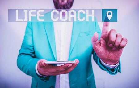 Handwriting text writing Life Coach. Conceptual photo someone who helps identify your goals and plan to achieve them Businessman in the blue suite with lap top pointing with finger