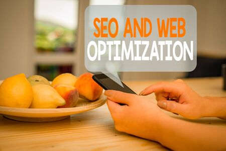 Word writing text Seo And Web Optimization. Business photo showcasing Search Engine Keywording Marketing Strategies woman using smartphone office supplies technological devices inside home Zdjęcie Seryjne