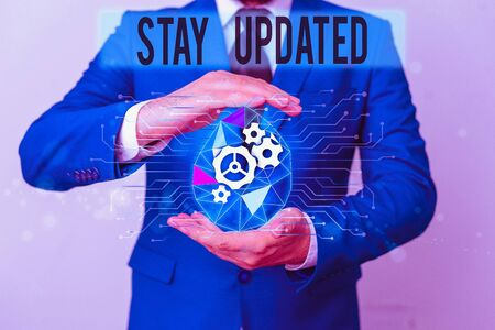 Conceptual hand writing showing Stay Updated. Concept meaning keep modern recent or containing the latest information Male human wear formal suit presenting using smart device