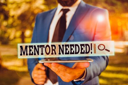 Handwriting text Mentor Needed. Conceptual photo Employee training under senior assigned act as advisor Businessman in blue suite stands with mobile phone in hands