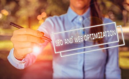 Word writing text Seo And Web Optimization. Business photo showcasing Search Engine Keywording Marketing Strategies Woman in a blue business shirts pointing with her finger into empty space