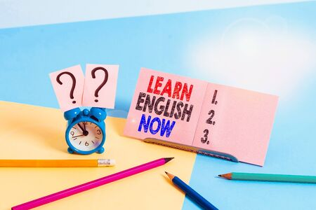 Conceptual hand writing showing Learn English Now. Concept meaning gain or acquire knowledge and skill of english language Mini size alarm clock beside stationary on pastel backdrop
