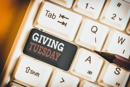 Writing note showing Giving Tuesday. Business concept for international day of charitable giving Hashtag activism White pc keyboard with note paper above the white background
