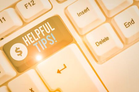 Text sign showing Helpful Tips. Business photo showcasing advices given to be helpful knowledge in life White pc keyboard with empty note paper above white background key copy space Banco de Imagens