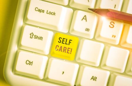 Conceptual hand writing showing Self Care. Concept meaning the practice of taking action to improve one s is own health White pc keyboard with note paper above the white background