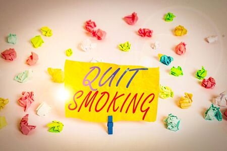 Word writing text Quit Smoking. Business photo showcasing process of discontinuing tobacco smoking or cessation Colored crumpled papers empty reminder white floor background clothespin