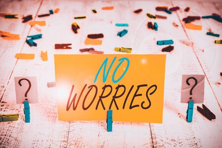 Writing note showing No Worries. Business concept for an expression used to say that everything is all right Crumbling sheet with paper clips placed on the wooden table