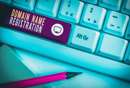 Writing note showing Domain Name Registration. Business concept for Own an IP Address Identify a particular Webpage White pc keyboard with note paper above the white background Stock Photo
