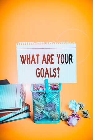Handwriting text What Are Your Goals Question. Conceptual photo ask the Desired End Results to know the plans Trash bin crumpled paper clothespin empty reminder office supplies yellow Фото со стока