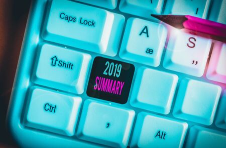Word writing text 2019 Summary. Business photo showcasing brief comprehensive especially covering the main points of 2019 White pc keyboard with empty note paper above white background key copy space Фото со стока