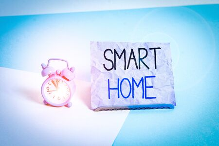 Handwriting text writing Smart Home. Conceptual photo automation system control lighting climate entertainment systems Mini size alarm clock beside a Paper sheet placed tilted on pastel backdrop