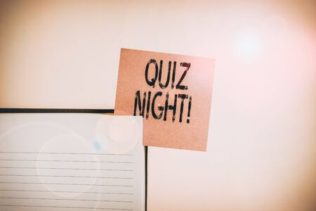 Text sign showing Quiz Night. Business photo showcasing evening test knowledge competition between individuals Upper view lined hard cover note book sticky note inserted clear background