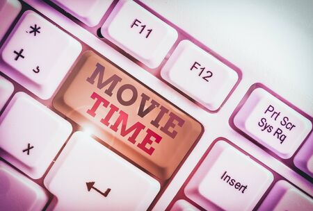 Handwriting text writing Movie Time. Conceptual photo the scheduled or actual time at which a show or film begins White pc keyboard with empty note paper above white background key copy space