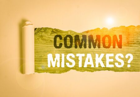 Writing note showing Common Mistakes question. Business concept for repeat act or judgement misguided or wrong Cardboard which is torn placed above a wooden classic table
