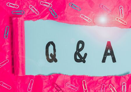 Handwriting text Q And A. Conceptual photo defined as questions being asked and answers Paper clip and torn cardboard placed above a plain pastel table backdrop