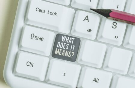 Handwriting text What Does It Means question. Conceptual photo asking someone about meaning something said and you do not understand White pc keyboard with empty note paper above white background key copy space Фото со стока