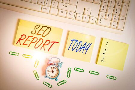 Handwriting text Seo Report. Conceptual photo notifying on how website is performing in search engine results Empty orange square papers and clock by the pc keyboard with copy space