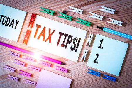 Handwriting text writing Tax Tips. Conceptual photo compulsory contribution to state revenue levied by government Colored clothespin papers empty reminder wooden floor background office