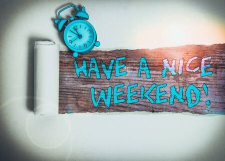 Handwriting text writing Have A Nice Weekend. Conceptual photo wishing someone that something nice happen holiday Alarm clock and torn cardboard placed above a wooden classic table backdrop