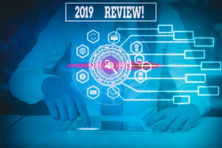 Writing note showing 2019 Review. Business concept for remembering past year events main actions or good shows Woman wear formal work suit present using smart latest device Фото со стока