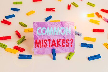 Writing note showing Common Mistakes Question. Business concept for repeat act or judgement misguided making something wrong Colored clothespin papers empty reminder white floor background office Фото со стока