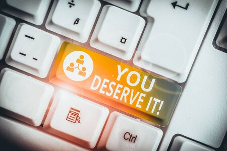Writing note showing You Deserve It. Business concept for should have it because of their qualities or actions White pc keyboard with note paper above the white background Фото со стока