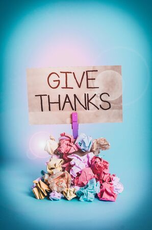Word writing text Give Thanks. Business photo showcasing express gratitude or show appreciation Acknowledge the kindness Reminder pile colored crumpled paper clothespin reminder blue background