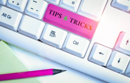 Writing note showing Tips And Tricks. Business concept for Steps Lifehacks Handy advice Recommendations Skills White pc keyboard with note paper above the white background