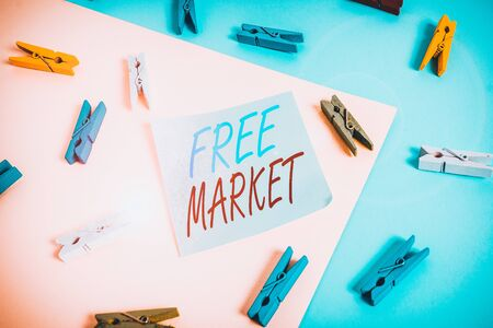 Text sign showing Free Market. Business photo showcasing an unregulated system of economic exchange or free competition Colored clothespin paper empty reminder yellow blue floor background office