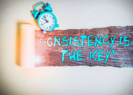 Handwriting text writing Consistency Is The Key. Conceptual photo by Breaking Bad Habits and Forming Good Ones Alarm clock and torn cardboard placed above a wooden classic table backdrop Foto de archivo