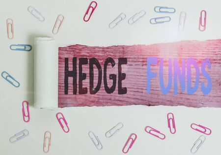 Text sign showing Hedge Funds. Business photo text basically a fancy name for an alternative investment partnership Paper clip and torn cardboard placed above a wooden classic table backdrop