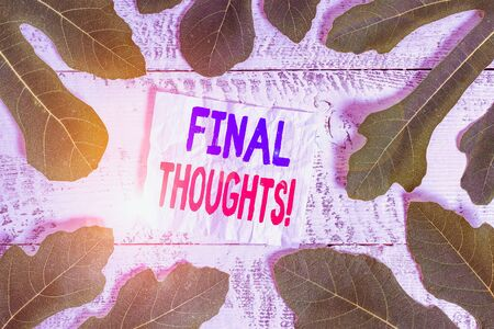 Text sign showing Final Thoughts. Business photo showcasing the conclusion or last few sentences within your conclusion Leaves surrounding notepaper above a classic wooden table as the background