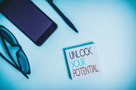 Handwriting text writing Unlock Your Potential. Conceptual photo improve self awareness Skills to Achieve more Eyeglasses colored sticky note smartphone cell pen cool pastel background Stock Photo