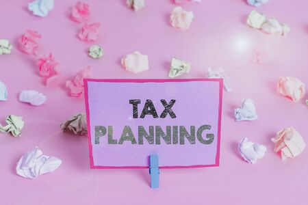 Writing note showing Tax Planning. Business concept for analysis of financial situation or plan from a tax perspective Colored crumpled papers empty reminder pink floor background clothespin 写真素材