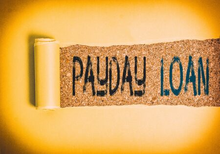 Text sign showing Payday Loan. Business photo text Something lent or furnished on condition being returned Cardboard which is torn in the middle placed above a wooden classic table 写真素材