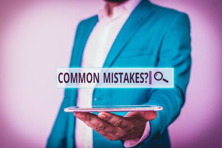 Conceptual hand writing showing Common Mistakes question. Concept meaning repeat act or judgement misguided or wrong Man in blue suite and white shirt holds mobile phone in hand Фото со стока
