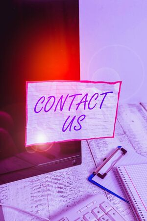 Text sign showing Contact Us. Business photo text Term used to describe reaching out with the business or demonstrating Note paper taped to black computer screen near keyboard and stationary