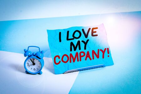 Writing note showing I Love My Company. Business concept for tell why admire their job and workplace Alarm clock beside a Paper sheet placed on pastel backdrop 写真素材