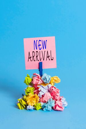 Text sign showing New Arrival. Business photo showcasing the introduction of something new such as a product or service Reminder pile colored crumpled paper clothespin reminder blue background