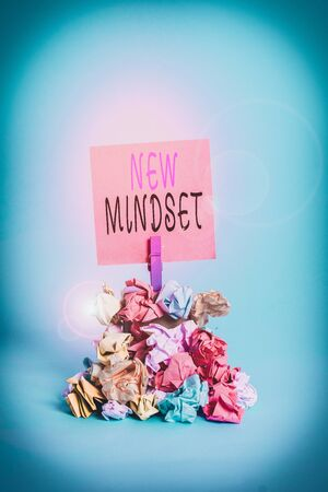 Text sign showing New Mindset. Business photo showcasing Mental attitude or disposition New approach in dealing situation Reminder pile colored crumpled paper clothespin reminder blue background