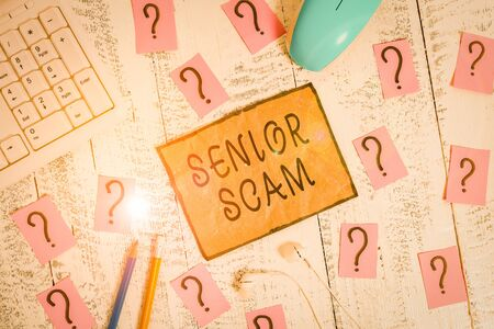 Conceptual hand writing showing Senior Scam. Concept meaning fraud schemes targeting the lifestyle and savings of the elderly Writing tools and scribbled paper on top of the wooden table