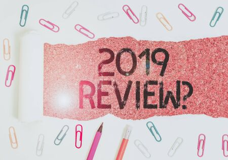 Text sign showing 2019 Review Question. Business photo showcasing remembering past year events main actions or good shows Stationary and torn cardboard placed above a wooden classic table backdrop