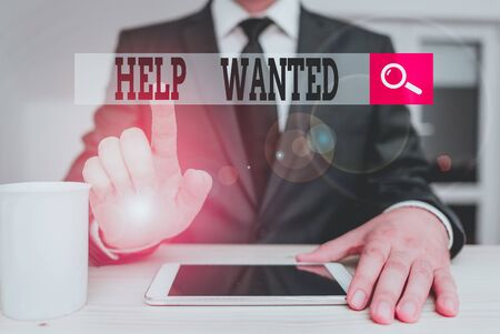 Conceptual hand writing showing Help Wanted. Concept meaning An ad in the paper an employer places to find a new employee Male human wear formal clothes present use hitech smartphone