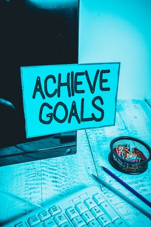 Conceptual hand writing showing Achieve Goals. Concept meaning Results oriented Reach Target Effective Planning Succeed Note paper taped to black screen near keyboard stationary 스톡 콘텐츠