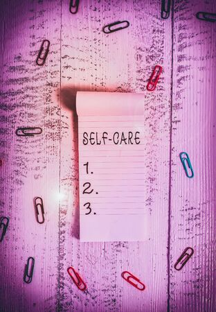 Text sign showing Self Care. Business photo showcasing the practice of taking action to improve one s is own health Stripped ruled notepad clips lying wooden old retro vintage background