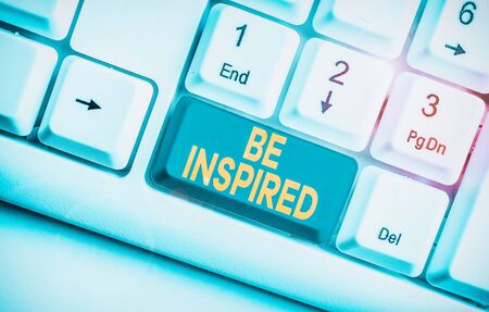Writing note showing Be Inspired. Business concept for give oneself the desire or enthusiasm to do something well White pc keyboard with note paper above the white background