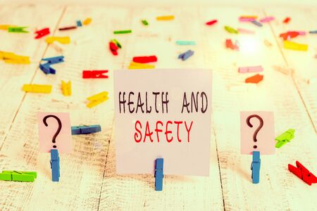 Writing note showing Health And Safety question. Business concept for regulations and procedures to prevent accident Crumbling sheet with paper clips placed on the wooden table
