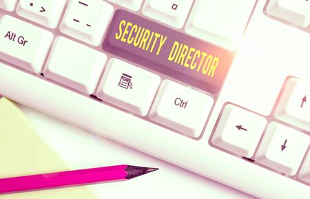 Conceptual hand writing showing Security Director. Concept meaning head of a private security force working for a business White pc keyboard with note paper above the white background Stok Fotoğraf